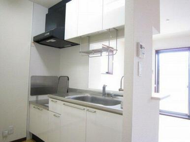 キッチンは対面式。吊戸棚を設けて収納量を確保!清潔感溢れるホワイト色も好印象。