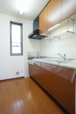 小窓付きのキッチンスペース。吊り戸棚付きで収納量も豊富。