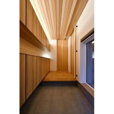 木目が美しい玄関ホール。壁一面のシューズボックスがあり玄関を彩るデザインにもなっています。