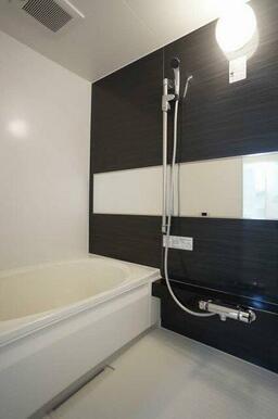 【浴室】アクセントパネルの映える浴室。ワイドタイプのミラーやシャンプーボトルなどを置けるカウンター、