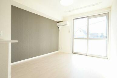 【LDK】白を基調とした壁と床に一面にだけアクセントとなるクロスでオシャレな空間を演出。エアコンは備