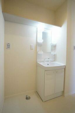 【洗面所】シャワー付きの洗面化粧台や室内洗濯機置き場があります。上にある棚はタオルや備品類を置けて便