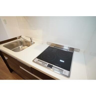 キッチンは2口のIHヒーターがビルトインされたシステムキッチンです。囲み壁をキッチンパネルで仕上げて