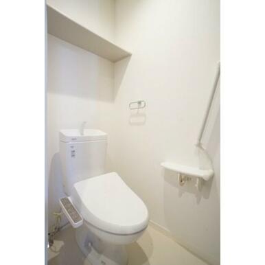 白調に統一され清潔感のあるトイレ。天井近くの小物棚が便利です。暖房洗浄便座有。肘掛一体の手すりが設置