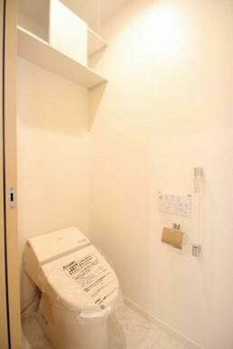 多機能便座を設置しております。壁に手すりや上部に備品が収納できる収納棚が設置されております。