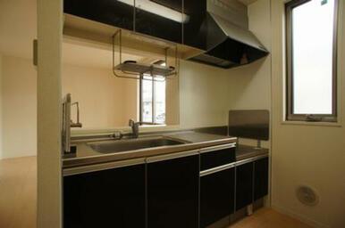 【LDK】キッチンは黒系色で引き締まった印象です◆スゥイング式の窓があり、換気に便利です。