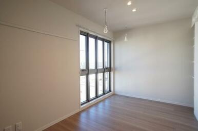 おしゃれな格子窓の室内物干し、洋服や絵などが掛けられる可動式壁フック、LED照明付の洋室です。