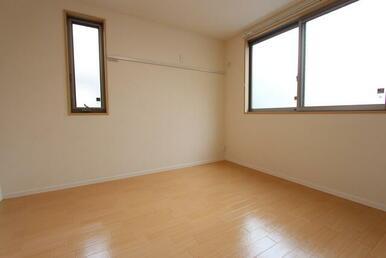 2面に窓のある明るい、LED照明、洋服や絵などが掛けられる可動式壁フック付の洋室です。