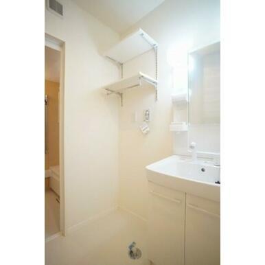 白基調でまとめた洗面室~浴室。洗濯機スペースの上にはガチャレールを採用した棚が既設です。