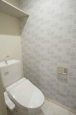 おしゃれなアクセントクロス、暖房洗浄便座付トイレです。上部に収納棚も付いてます。