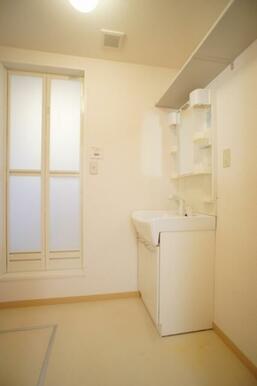 脱衣所には独立洗面化粧台を装備しています◆右手前は洗濯機置き場です◆上部には収納棚があり、意外と重宝