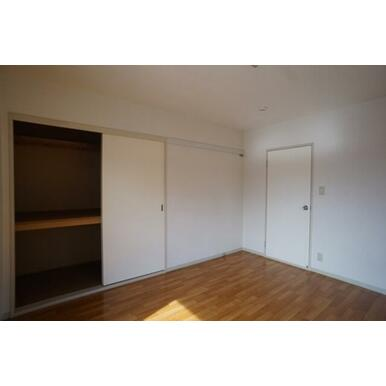 洋服や絵などが掛けられる可動式壁フック、収納付の洋室です。