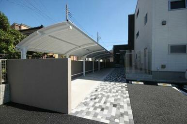 駐車場からエントランスにかけて広い屋根付き駐輪場。自転車やバイクが十分に置けます。