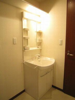 ノズルが伸びて洗髪も可能な洗面化粧台。隣は洗濯機置場です。スペース上部には収納棚も付いています。