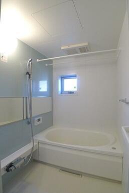 浴室の一面には空間のアクセントとしてライトブルーのフィルム貼りを施工♪また上部には浴室乾燥機&物干し