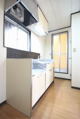 吊戸棚付きのキッチン。収納量は豊富です。引き違いの窓も付いていて、通気性も良好です。
